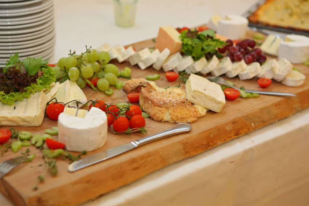 cheeseboard with grapes and tomatoes. A selection of difference cheese on a wooden board