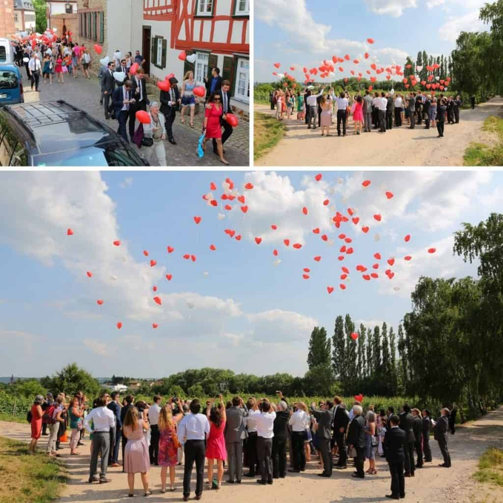 Wedding guests with heart shaped wedding baloons, letting them rise above vinyards