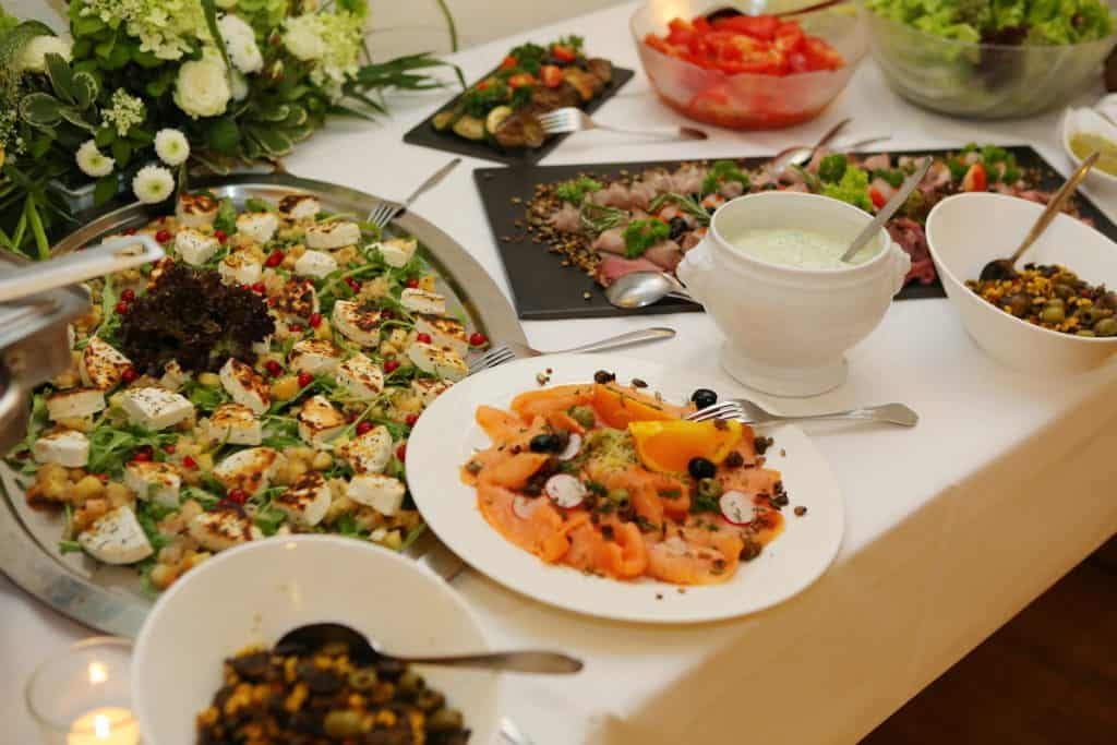 German Wedding Starters - Goatscheese, Smoked Salmon, Horesradish sauce, Selection of salads on a table with white table cloth