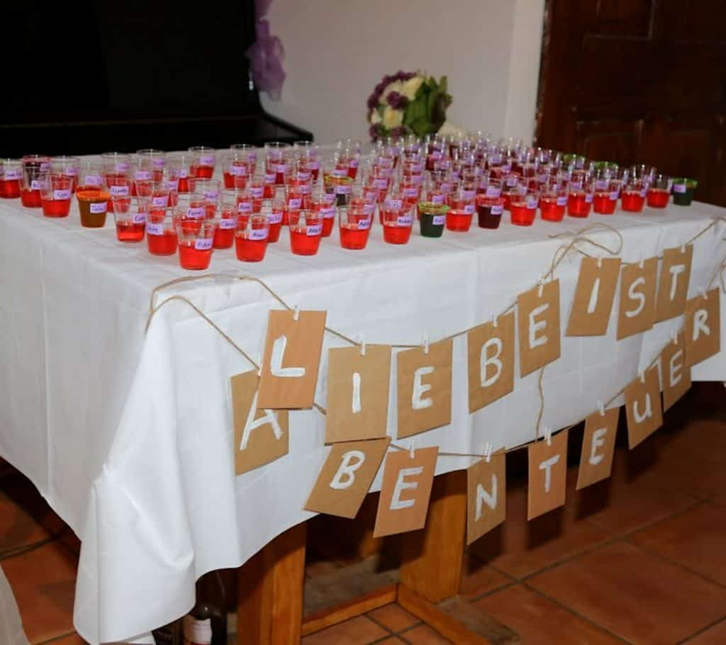 """DIY Wedding Seating Chart with Homemade Strawberry Vodka. Underneath there is some signage saying """"Liebe ist Arbenteuer"""" - Love is adventure"""