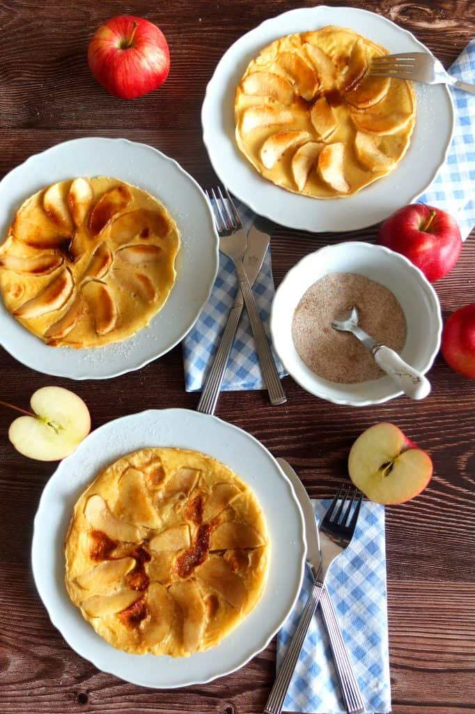 A wooden table top. On the table on white plates you can see three apple pancakes. A bowl of cinnamon sgar and two apples. One apple is slices in alf. The plates have blue and white
