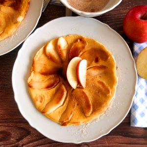 German apple pancake on a white plate that is set on a wooden background. On top of the pancakes there are two apple slices. Around the pancake there you can see a bowl of cinnamon sugar, an apple and part of a plate with another pancake