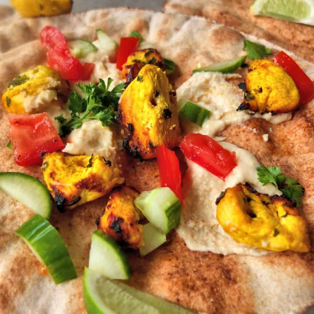 A pita bread topped with hummus, cucumbers, chicken and tomatoes