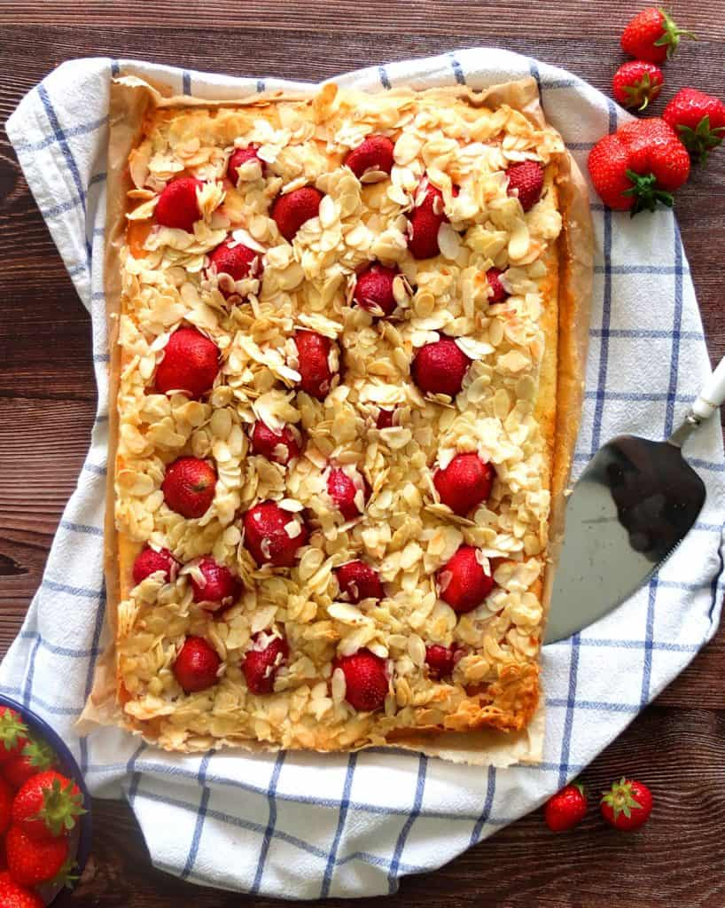 A strawberry almond cake on a white and towel, surrounded by loose strawberries