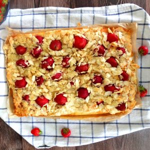 Blitzkuchen - a cake with almond and frozen strawberries on a blue and white tea towel