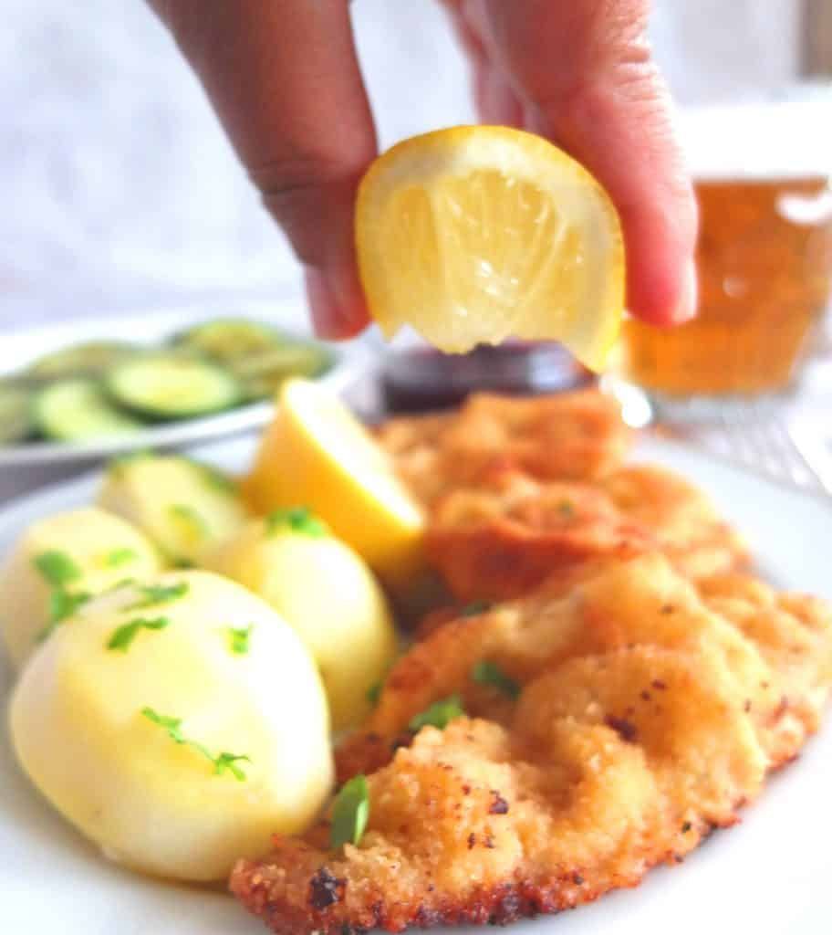 A Wiener Schnitzel on Parley potatoes on a white plate. Above you can see a lemon being squeezed over the