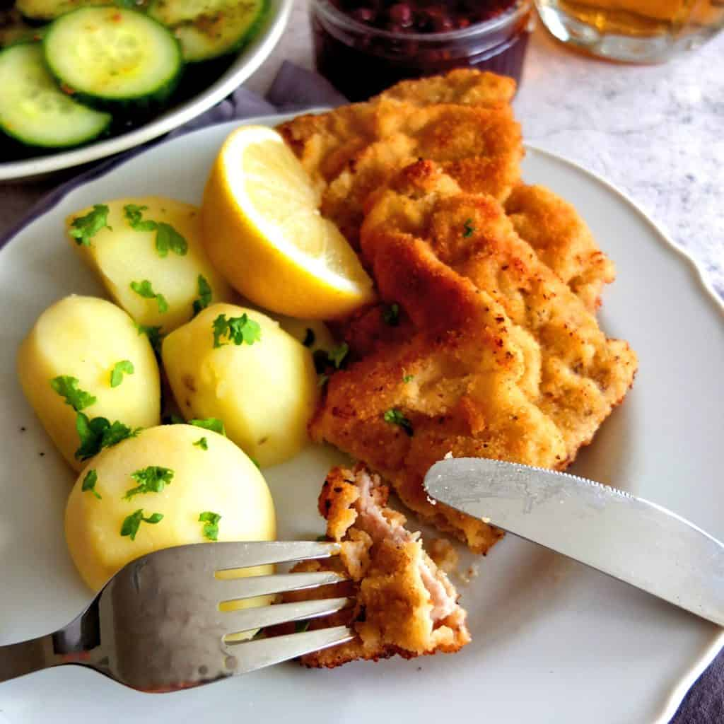 Viennese Schnitzel on a plate with parsley potatoes. A knife in fort is shown and a bit of schnitzel is is cut of and pricked onto the fork. In the background there is cucumber salad and cranberry sauce