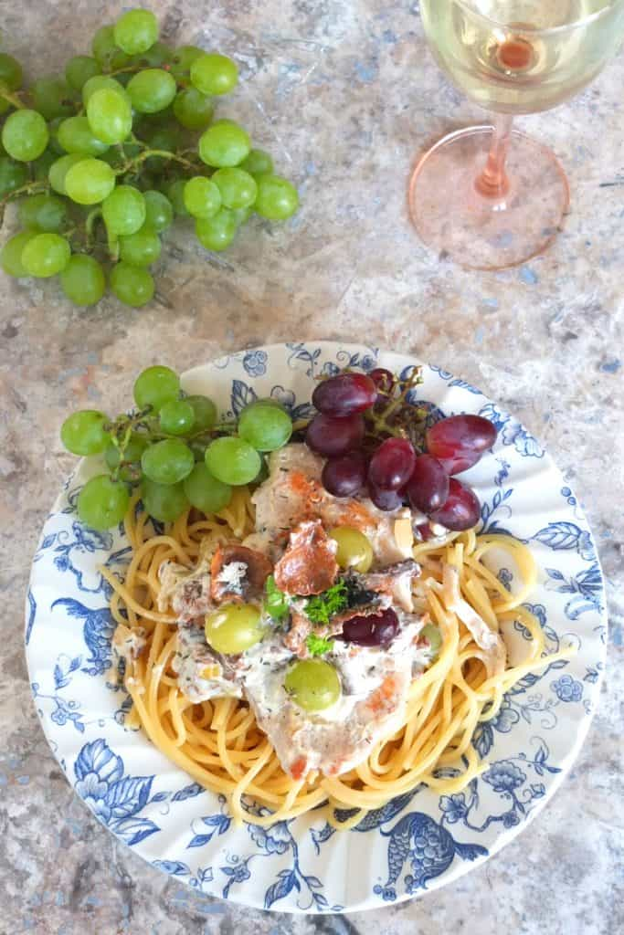 Chanterelle Pasta Recipe on a blue and white plate. At the bottom you can see some spagetti, topped with a chanterelle mushroom sauce and a schicken schnitzel. The dish is garnished with red and white grapes. In the background you can see a pune of green grapes and a glas of wine.