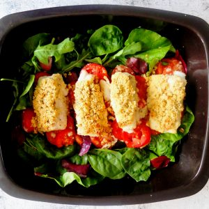 A black baking tray. On the baking tray there are some green lettuce leaves. On top of the lettuce leaves are potatoes and fish fillets The fish fillets in topped with breadcrumbs