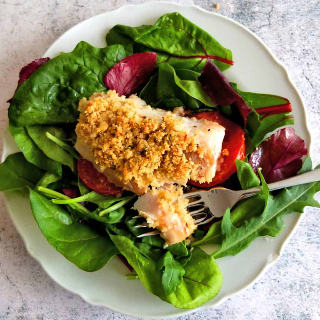 A white plate with green salad leaves. On top of the salad leaves is a piece of cod which has a breaded crust. A fork lies on the plate with a piece of cod broken off.