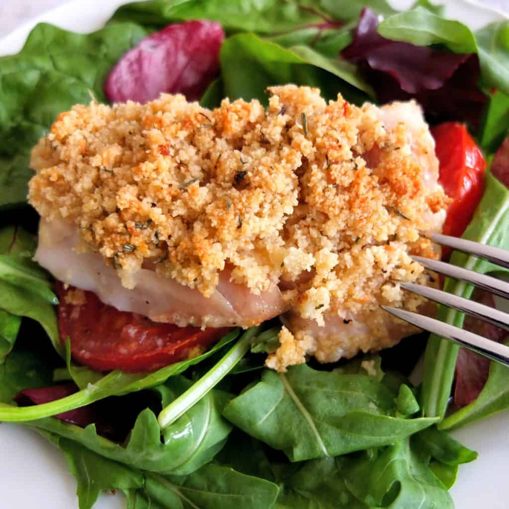 A piece of crusted cod on top of tomatoes which lay on some green salad leaves