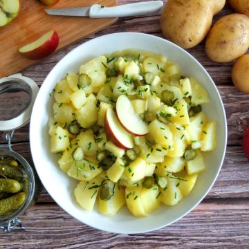 German Potato Salad on a White Plate. Around there is some cut up apple, a jar of Ghekins and some unpealed potatoes