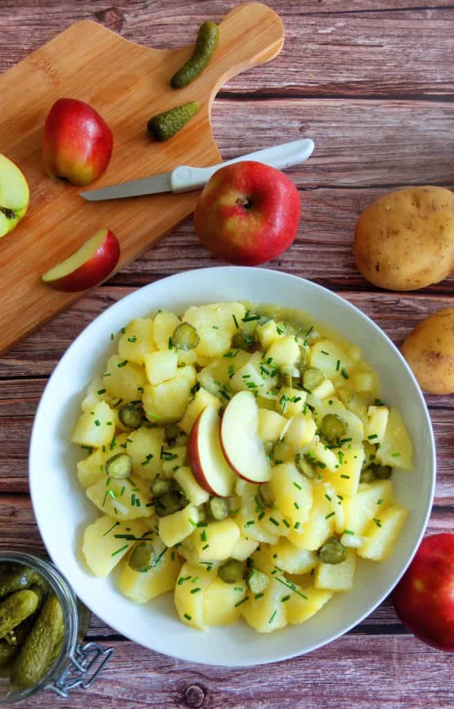 On top top you see a chopping board with cut up apples. Some raw potatoes and a jar of gherkins. In the middle of the picture is a white plate with potato salad