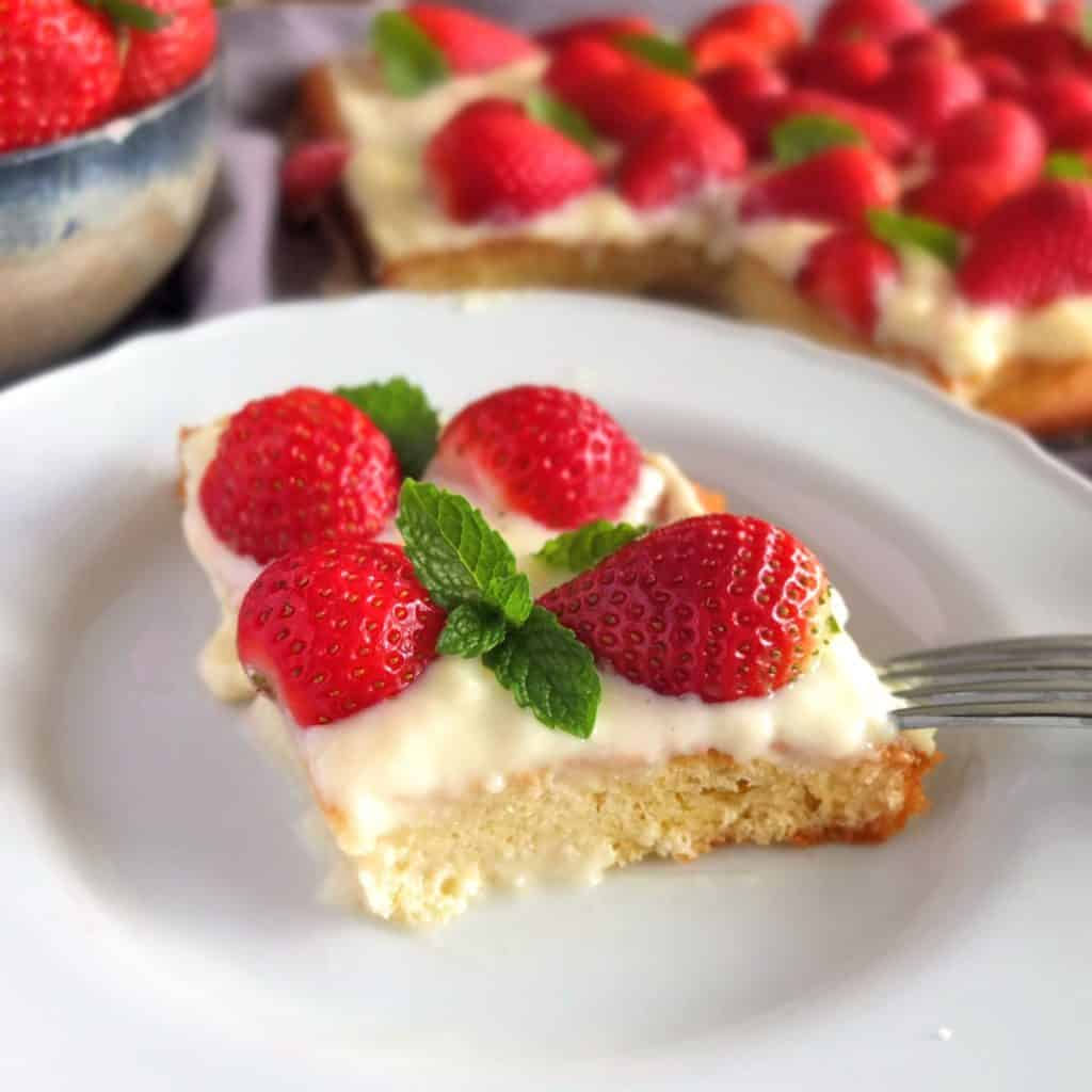 Slice of strawberry cake on plate with a fork. Cake is in the background