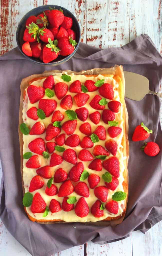 Strawberry Cake on a cloth with a bowl of strawberries