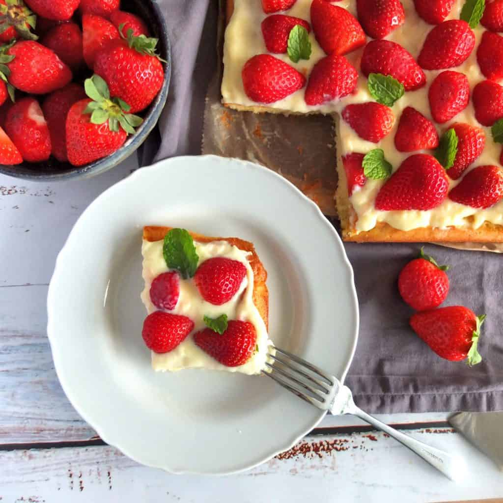 piece of strawberry tray bake on a plate. Cake in the background