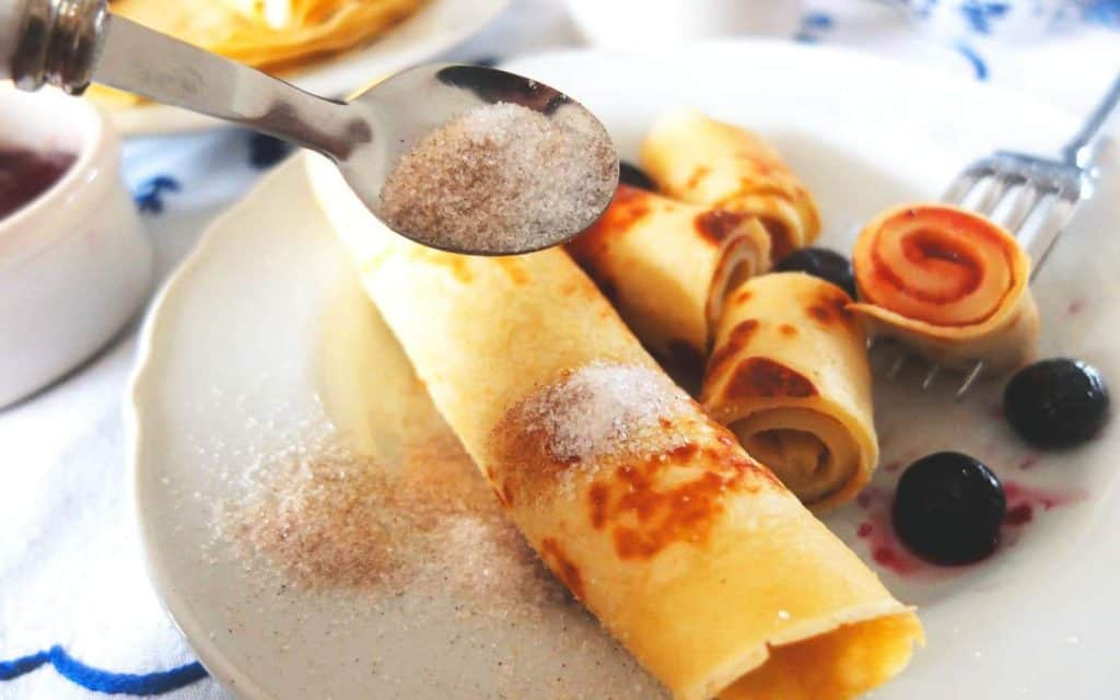 Cinnamon Sugar being spread over a German Pancake