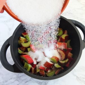 pouring sugar on top of sliced rhubarb