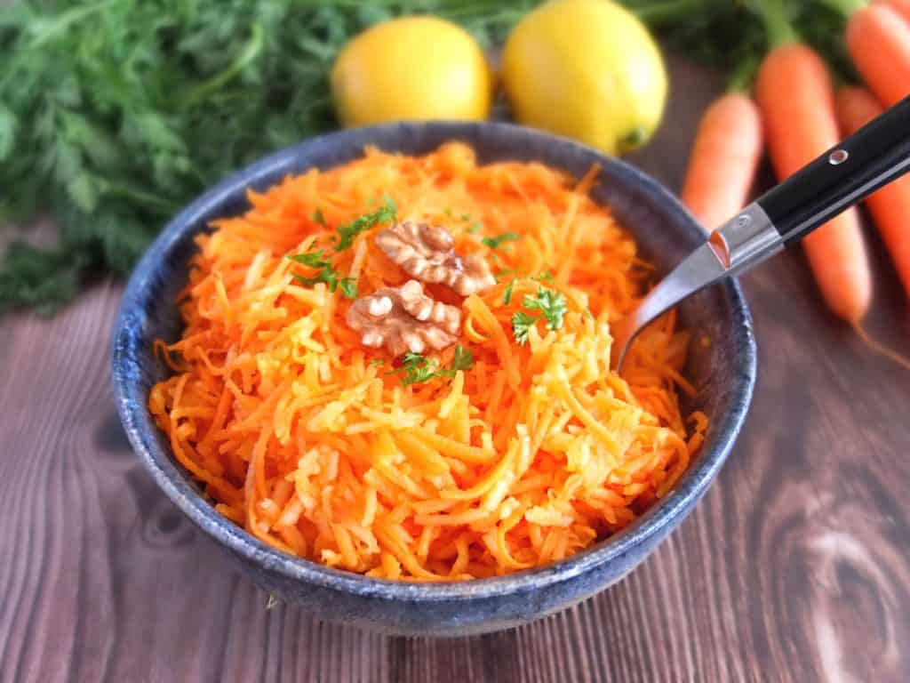 German carrot salad in a blue bowl. A fork is sticking in the salat. In the background you can see fresh carrots and lemons
