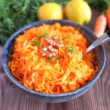 German Apple Carrot Salad with lemons and carrots in the background