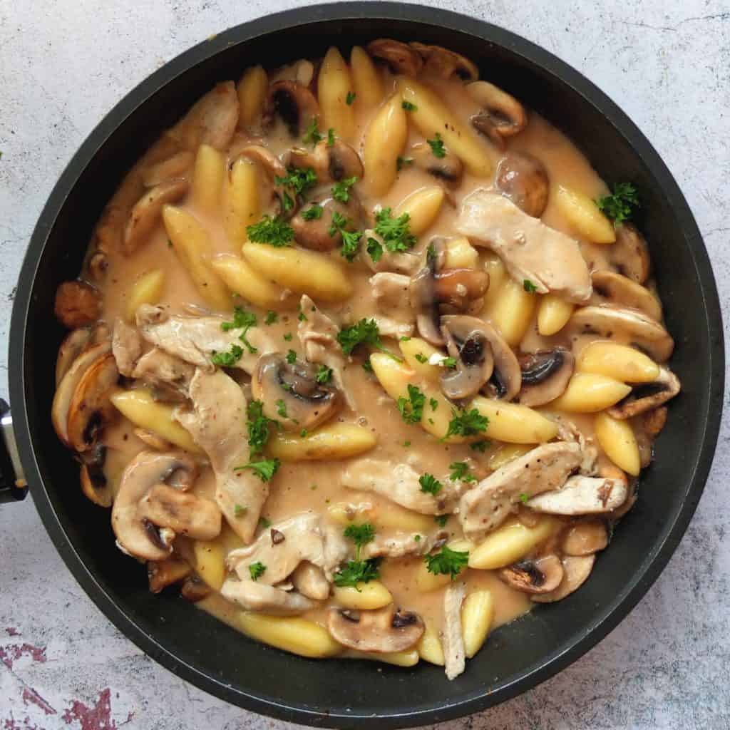 A pan with chicken, schupfnudeln, Mushrooms in Rahmsauce. Some chopped parsley is sprinkled on top
