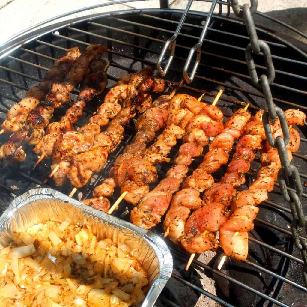 A bbq with pork belly skewers on the top. A tong is hovering of it. At the front you can see a aluminium bowl with onions