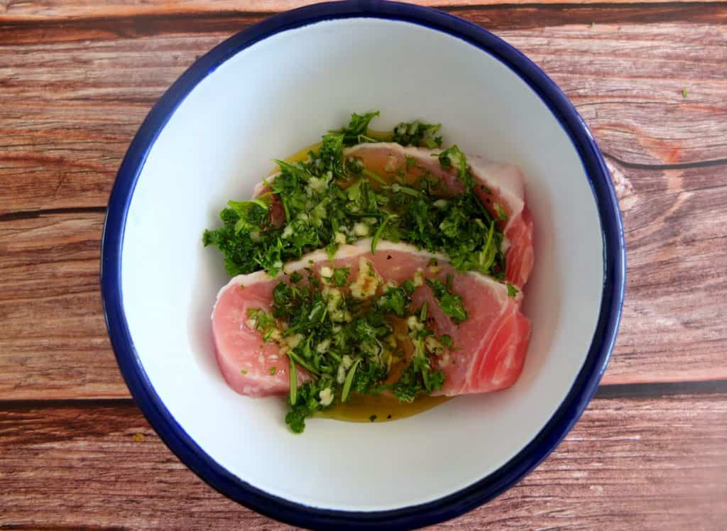 Schweinesteak in a Blue and White bowl with a green herb marinade on a wooden background