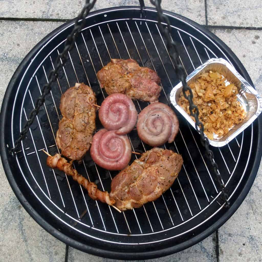 On a bbq you can see three pork steaks, one pork belly skewer and onions in a foil.