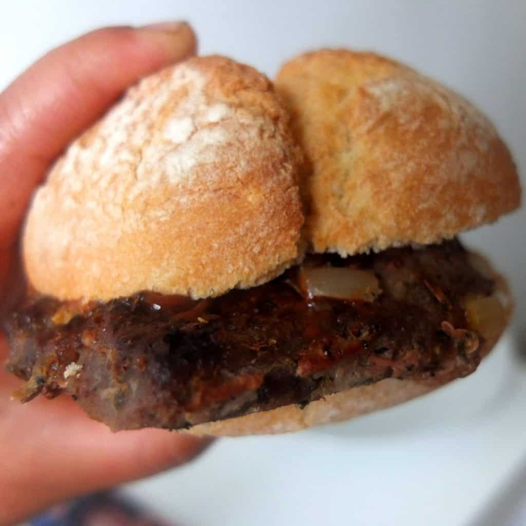 A hand holding a pork steak sandwich. The background it white