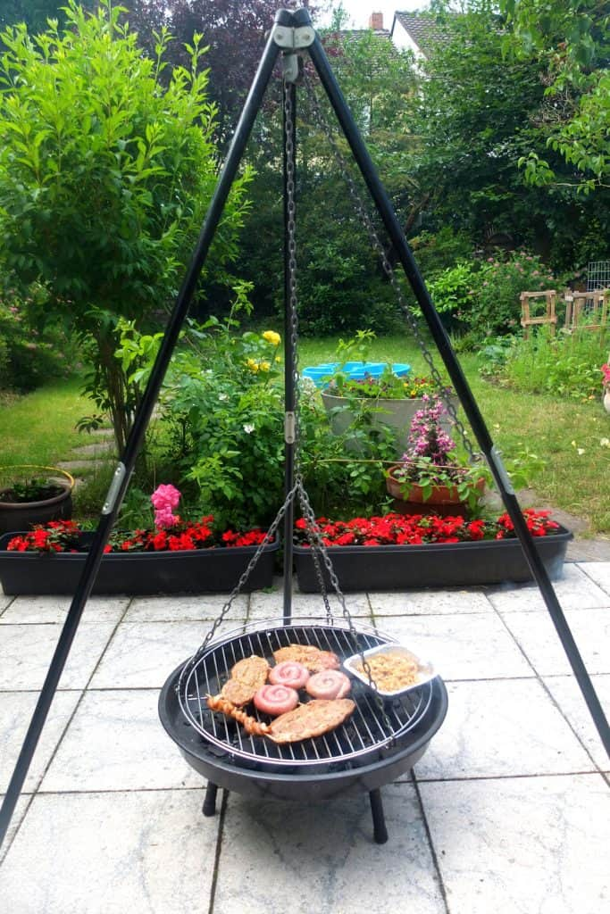 Schwenkgrill - a german grill on a tripod in a garden. On the grill you can see an array of meats