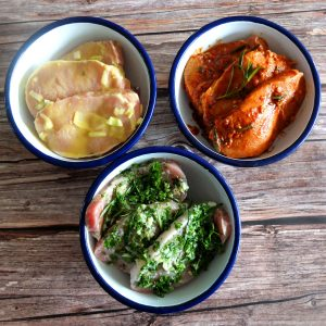 Three bowls with marinaded pork on a wooden surface. In the back a yellow marinade with mustard, and a red marinade with paprika. At the front a green her marinade
