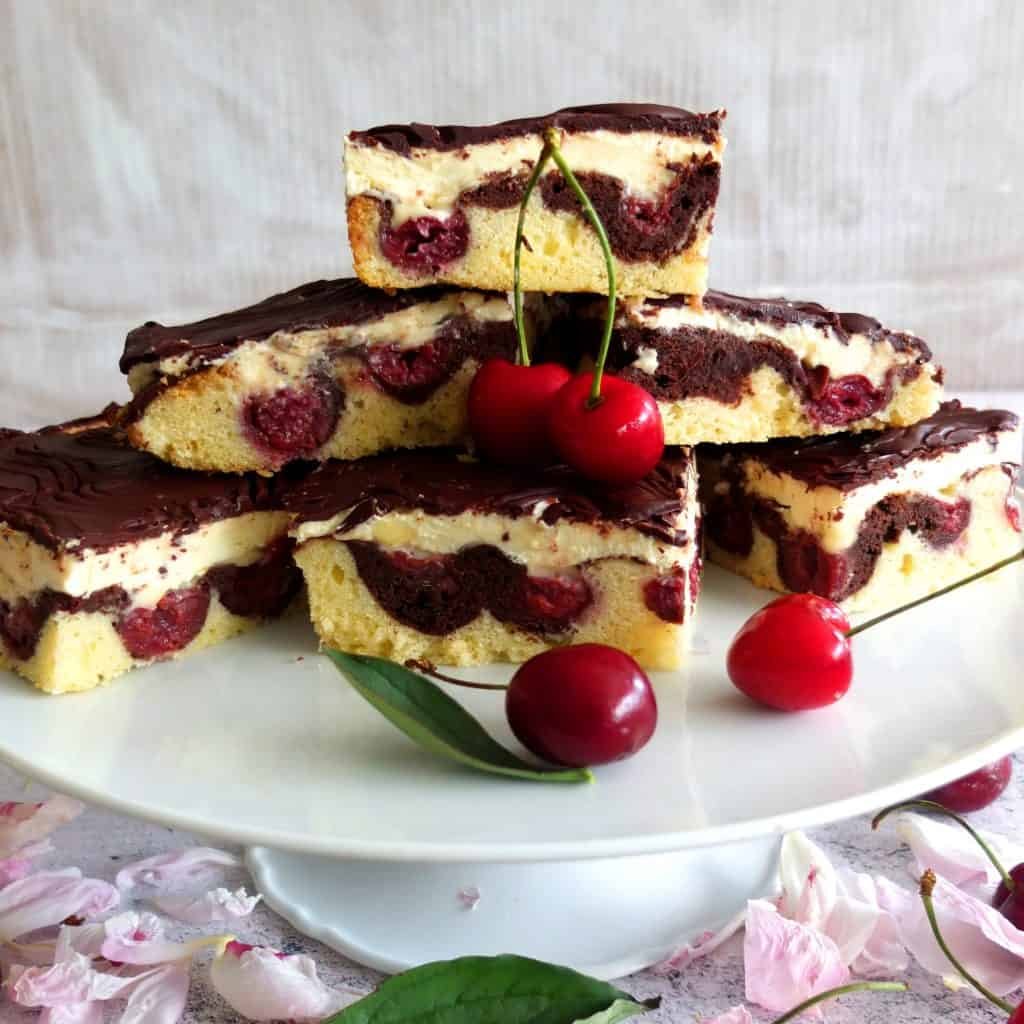 A cake stand with slices of Donauwellen Cake. The slices are build up to a pyramid. in front of the cake you can see two cherrys. Under the sand there are pink blossoms and cherries