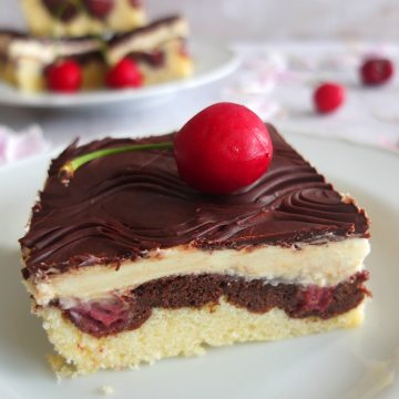 A slice of Danube Cake with a cherry on top. The slice of cake is topped by a cherry. In the background you can see a plate with more cake slices and some cherries.