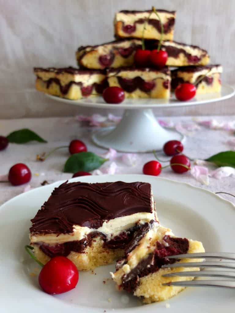 A slice of Donauwellen Cake on a white plate. A piece has been broken off with a fork. In the background you can see more Donauwellen pieces stabled up to a pyramid. They are on a cake stand. under the cake stands there are pink petals and more cherries.