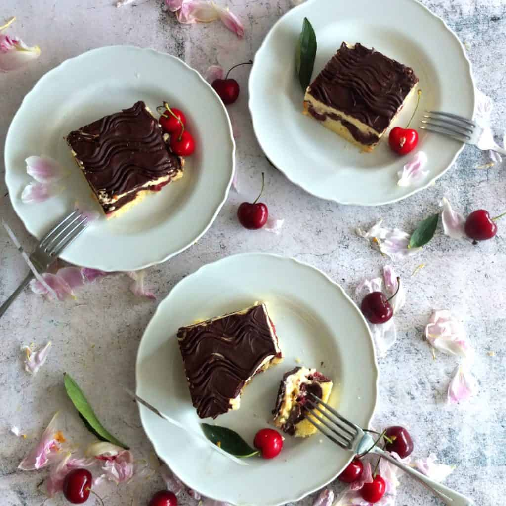 2 danube cakes on white plates. One piece is broken off with a fork. The plates are surrounded by cherries and pink petals