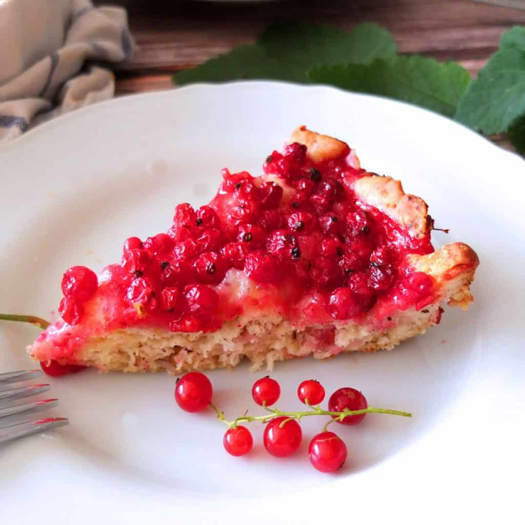 A slice of red currant cake on a white plate. In front of the cake you can see some red currant risps.