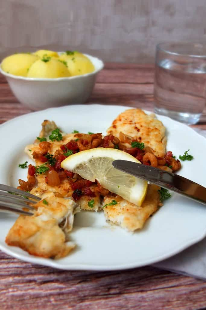 A white plate is in the foreground, which has a piece of fried cod topped with brown shrimp and bacon on it. Left and right there is a knife that has cut of a chunk of the fish. In the background you can see a bowl of potatoes and a glas with water.