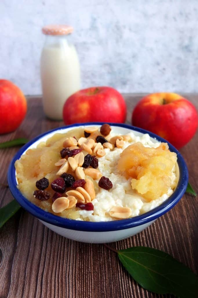 A white bowl with a blue rim. In the bowl is Milchreis, German rice pudding. The rice is topped with apple sauce and sprinkled with nuts and apples. In the background there are three apples and a glas bottle with milk.