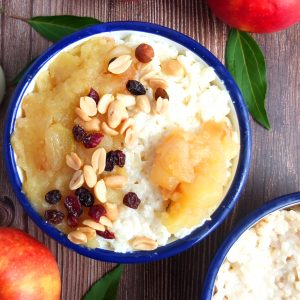 A bowl with a white rim. in the bowl there is Geman Rice Pudding. The toppig ins apple sauc, nuts and raisins. You can see parts of some red apple in the picture another bowl of milk rice in the corner