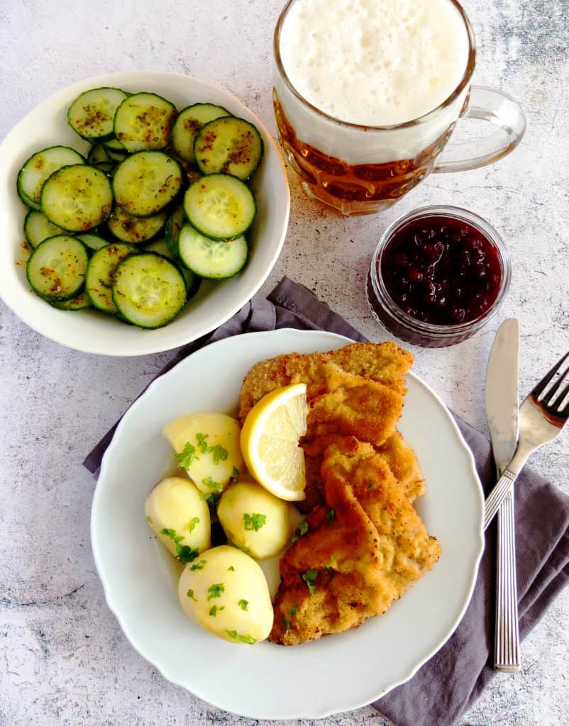 A white plate on a grey napkin. On the plate there is a Wiener Schnitzel with parsley potatoes and a slice of lemon. Above is a little pot with cranberry sauce. As a side dish you can see some cucumber salad to go along the wiener schnitzel. Right at the top you can see a glas of beer.