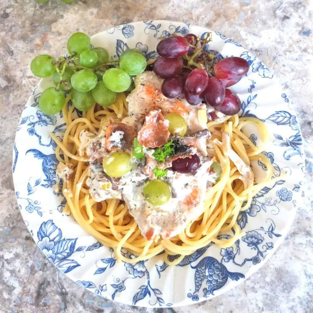 Chanterelle Pasta dish on a blue and white plate. You can see spagetti, on top there is a chicken schnitzel with a chanterelle mushroom sauce and some grapes.