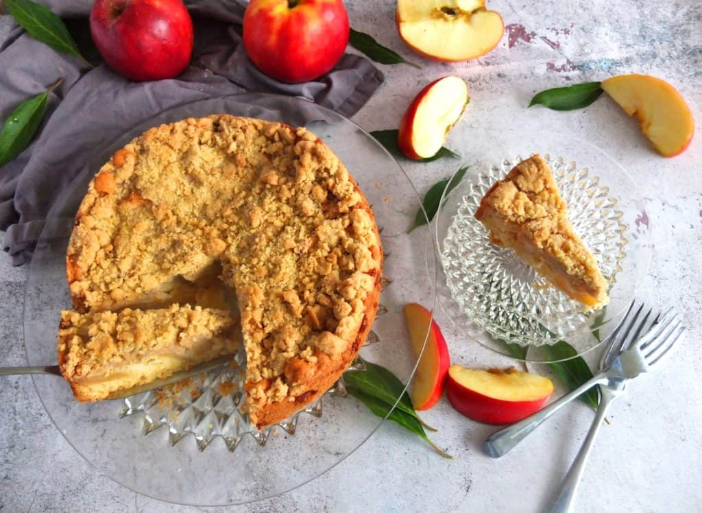 German Apple cake with streusel topping on a glass platter. One of the slices is being lifted out with a cake sliver. Next to the glass platter there is a slice of apple cake on a glas plate. Underneath you can see two forks and some slived apples and green leaves. Above the apple cake you have some red apples situated.