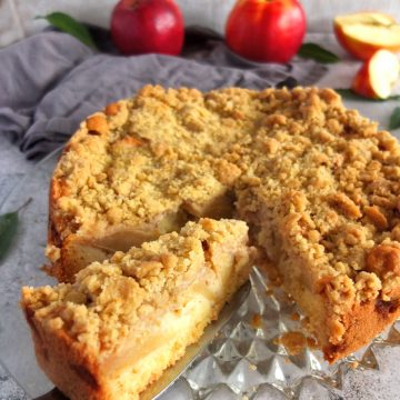 A German apple streusel cake on a glass plate. One of the slices is being lifted out with a cake slice. In the background there are some red apples. One red apple is sliced.