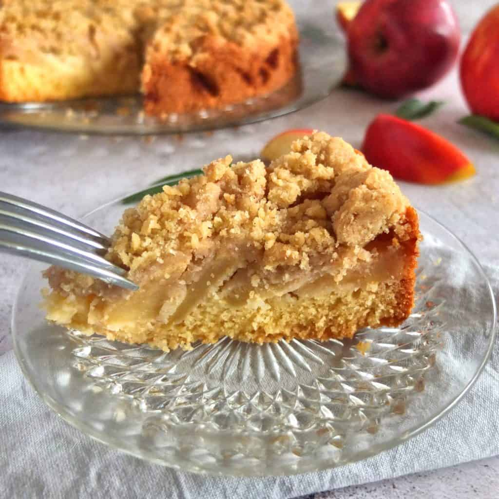 A piece of apple streusel cake on a grey background. A fork is breaking off a piece. in the background you can see the german apple streusel cake with some apples in the background. There are also some apple slices.