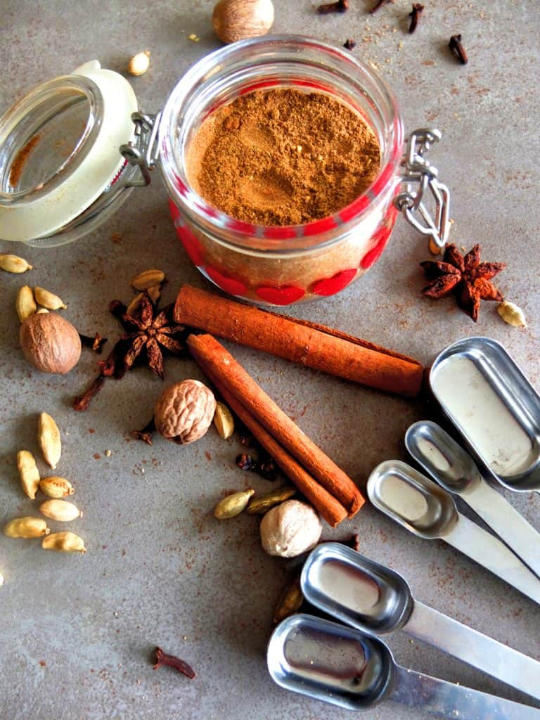 A glas jar of German gingerbread spice on a grey background. Around the glas jar you can see spices such as cinnamon, nutmeg, cardamon and cloves. On the corner of the picture you can see some measuring spoons