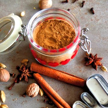 Lebkuchen Spice in a jar on a grez background. In front of the jar you can see cinnamon sticks, nutmegs, star anice. In the background there are some cloves. In the right corner you can see some measuring spoons