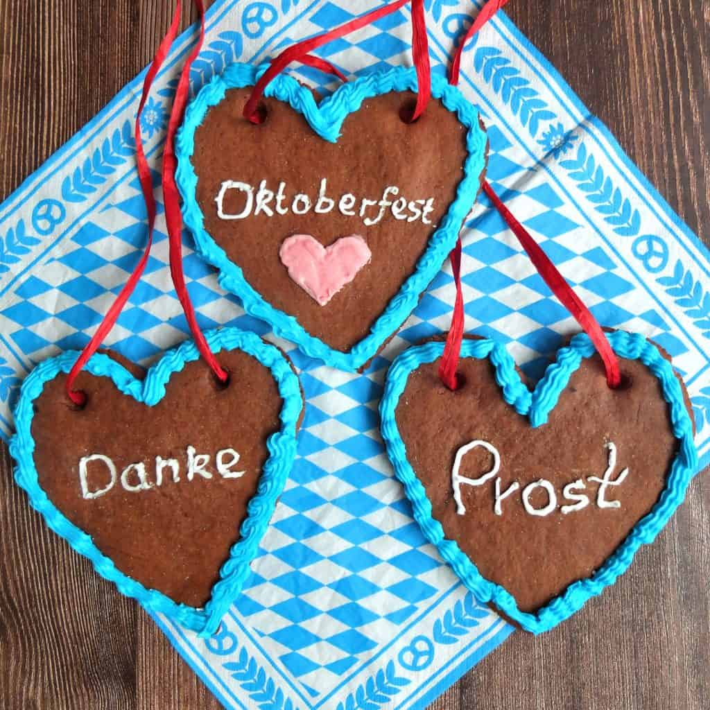 """Lebkuchenherzen (German Gingerbread hearts) on a bavarian blue and white napkin. The hearts are decorated with blue icing. The inscription say """"Danke (Thank you) """"Prost"""" Cheers"""" And Oktoberfest"""