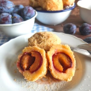Plum Dumplings cut open on a white plate. In the background you can see a bowl of Italian prune plums and another bowl with Dumplings