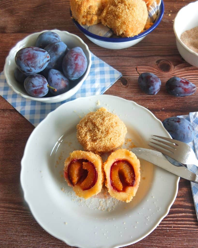 Zwedgenknödel (German Plum Dumplings) cut in half on a white plate. In the background a bowl of Italian prune plums. A Knife and Fork is reasting against the plate