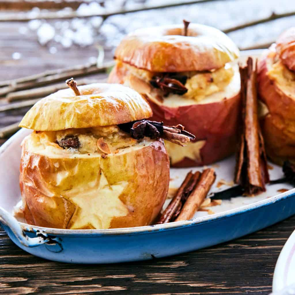 Baked or roasted apples with Christmas stars stuffed with fruit nuts and spices served on a metal plate at a winter BBQ on a snowy table